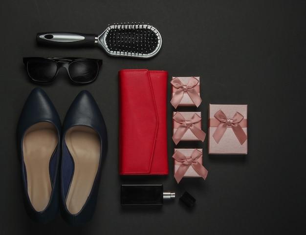 Damenaccessoires auf schwarzem hintergrund. schuhe mit hohen absätzen, kamm, sonnenbrille, parfümflasche, geldbörse, geschenkbox. geburtstag, muttertag, weihnachten. draufsicht