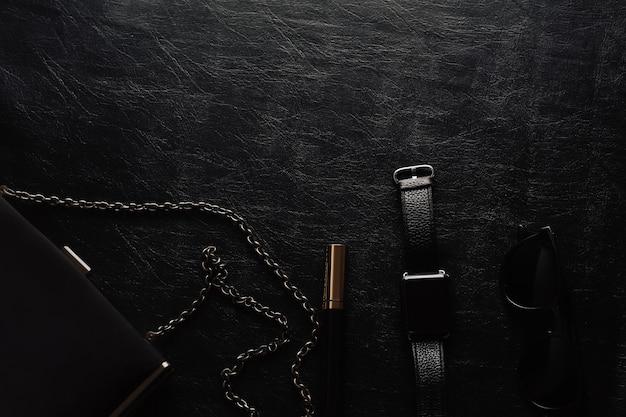 Damenaccessoires auf schwarzer wandwimperntusche, uhr, sonnenbrille und handtasche. schwarze monochromatische zusammensetzung. draufsicht.