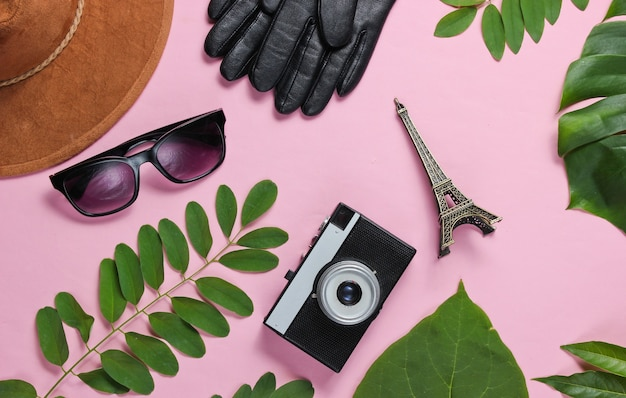 Damenaccessoires, retro-kamera, figur des eiffelturms auf rosa pastellhintergrund mit grünen blättern. draufsicht