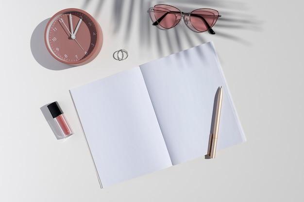 Damenaccessoires, trendiger palmblattschatten und geöffnetes leeres notizbuch
