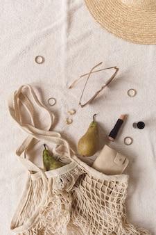 Damenaccessoires und bijouterie auf beiger decke. saitentasche, strohhut, sonnenbrille, lippenstift, ringe, ohrringe, birnen