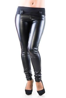 Damenbeine in schwarzen ledergamaschen und schwarzen schuhen mit hohen absätzen. auf weißem hintergrund isoliert