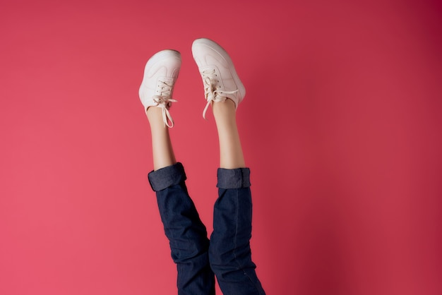 Damenbeine invertiert in weißen sneakers streetstyle