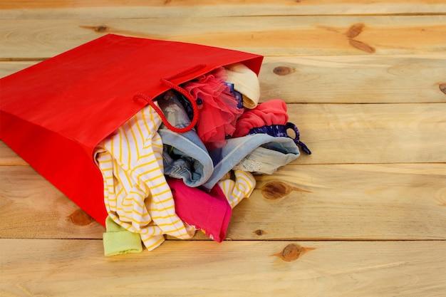 Damenbekleidung fällt aus papiereinkaufstüten.