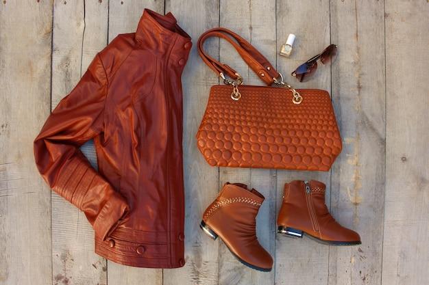 Damenbekleidung und accessoires auf alter holzoberfläche. draufsicht. flach liegen.