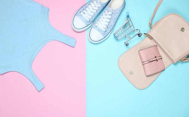 Damenbekleidung und accessoires auf pastell. turnschuhe, t-shirt, handtasche, mini-einkaufswagen