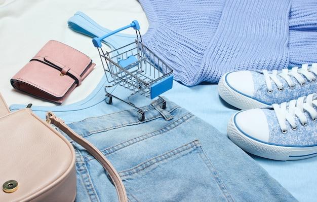 Damenbekleidung und accessoires. turnschuhe, t-shirt, handtasche, jeans, mini-einkaufswagen