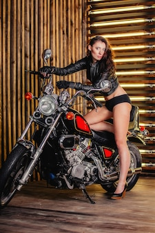 Damenbiker und hübsches mädchen mit dunklem haar, langes haar, erotik, das seine lederjacke und schwarze shorts und hochhackige schuhe aufknöpft, die auf einem motorrad auf dem hintergrund einer holzwand lehnen