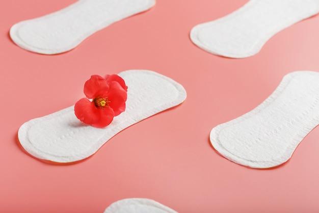 Damenbinde auf einem rosa hintergrund mit einer roten blume. freier platz für text.