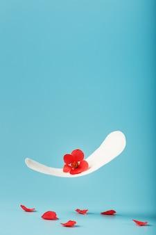 Damenbinde im flug auf einem blauen hintergrund mit gefallenen blütenblättern der roten blumen. konzept des beginns der wechseljahre.