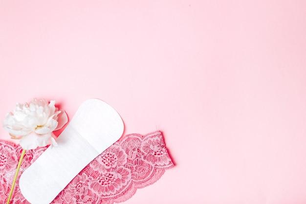 Damenbinde mit einer schönen pfingstrose und unterwäsche auf einer rosa oberfläche