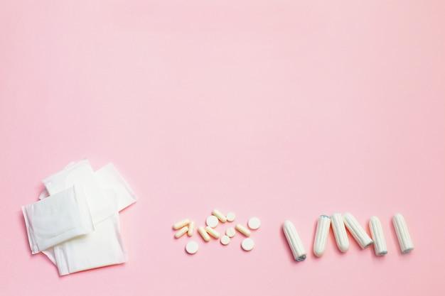 Damenbinden und saugfähige blätter auf rosa hintergrund