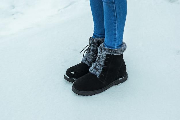 Damenfüße in jeans und warmen stiefeln mit fell auf dem schnee. schöne und praktische damen winterschuhe.