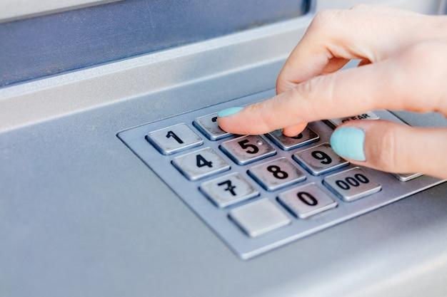 Damenhand wählt den pin-code an einem geldautomaten