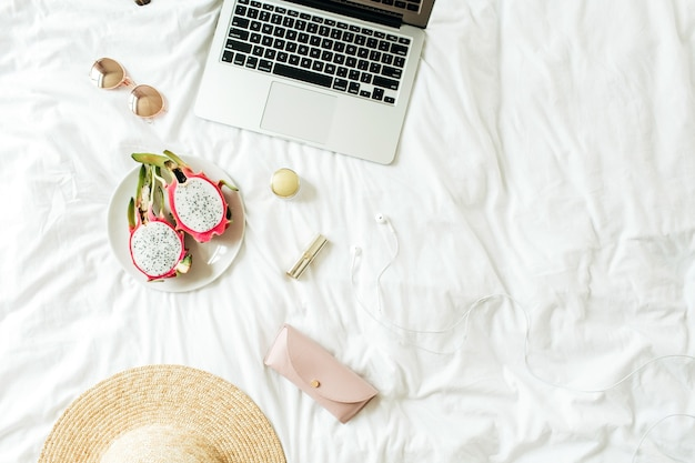 Damenmode-accessoires, brille, lippenstift, strohhut, etui, kopfhörer mit laptop und exotische drachenfrucht liegen mit weißer bettwäsche auf dem bett