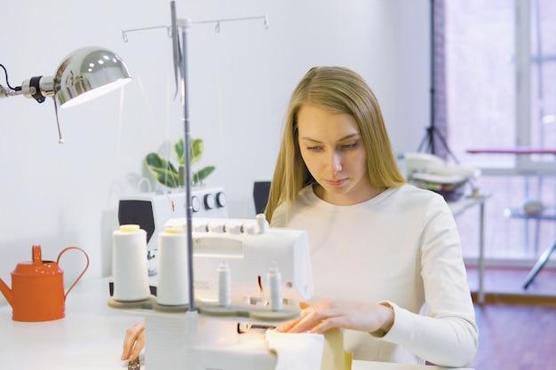 Damenschneiderinfrau, die mit nähmaschine in der werkstatt arbeitet