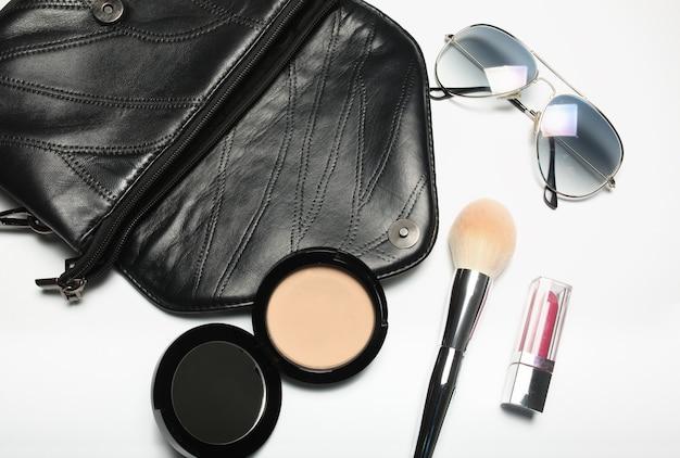 Damentasche mit sonnenbrille, kompaktpuder und lippenstift auf weißem hintergrund