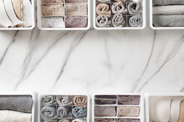 Damenunterwäsche, pyjama und socken ordentlich gefaltet und in schrank schublade teiler auf weißem marmortisch platziert.