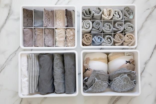 Damenunterwäsche pyjamas und socken ordentlich gefaltet und in schrank organizer schublade trennwand auf weißem marmortisch platziert