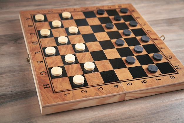 Damespiel auf schachbrett im hölzernen hintergrund.