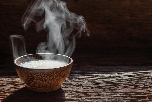 Dampf der asiatischen art des breis oder des gekochten reises mit rauche in der hölzernen schüssel auf dunklem hintergrund