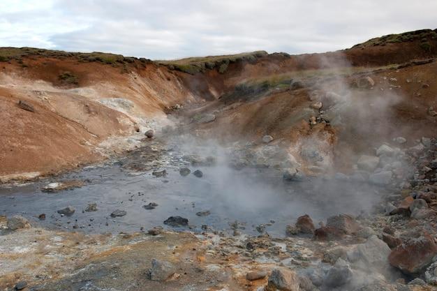 Dampf, der vom felsigen geothermischen pool steigt