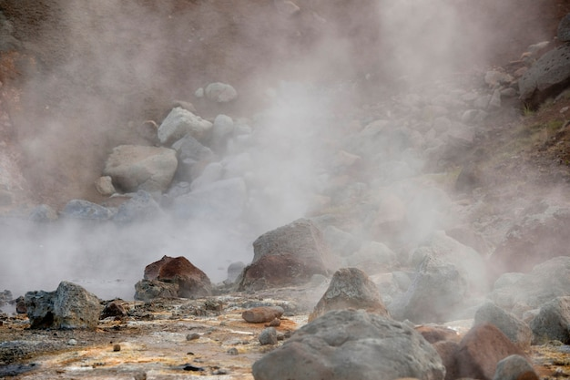 Dampf, der von den verstreuten landschaft der flusssteine steigt