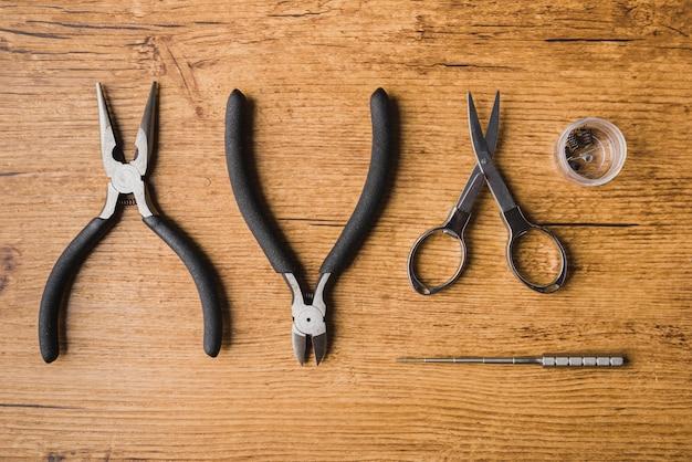 Dampfende werkzeuge mit hölzernem hintergrund, scisors, zerstäuber, spule