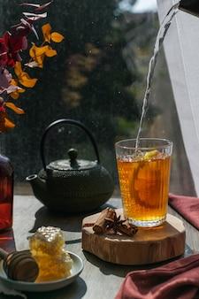 Dampfender heißer tee mit zitrone, herbstlaub und bienenwabe