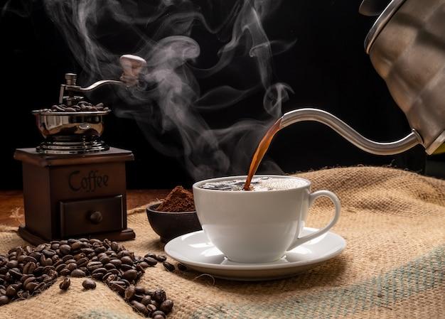 Dampfkaffeetasse mit mühle, gerösteten bienen, gemahlenem kaffee und kessel über sackleinenhessisch auf grunge-holztischhintergrund