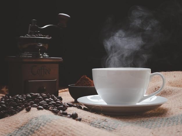 Dampfkaffeetasse mit mühle, gerösteten bienen, kaffeemehl über sackleinenhessisch auf grunge-holztischhintergrund