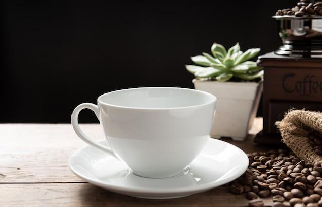 Dampfkaffeetasse mit mühle, gerösteten bohnen und blumentopf auf holzhintergrund im morgensonnenlicht