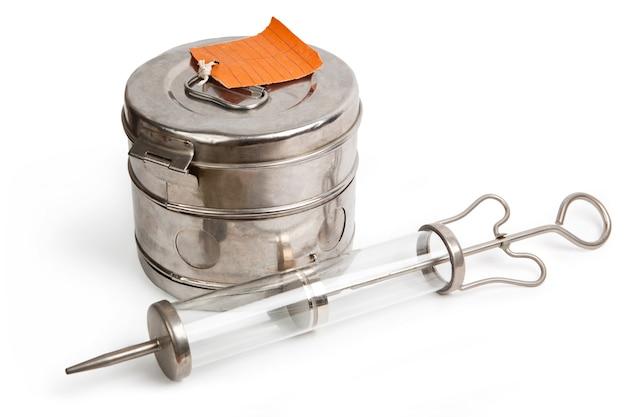 Dampfsterilisator und große spritze mit dicker nadel isoliert auf weiß