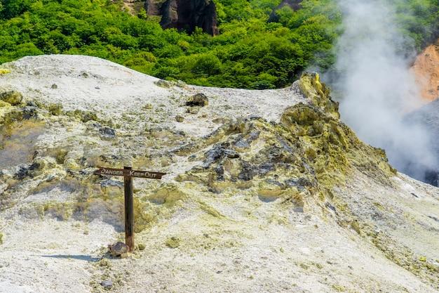 Dampfwasser und schwefel auf dem steinberg in jigokudani-tal, noboribetsu, hokkaido, japan