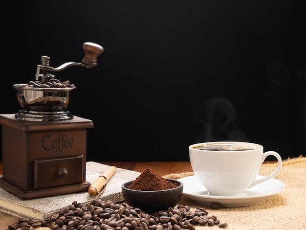 Dampfweiße kaffeetasse mit mühle, gerösteten bohnen, kaffeepulver und notizbuch über sackleinenhessisch auf grunge-holztischhintergrund