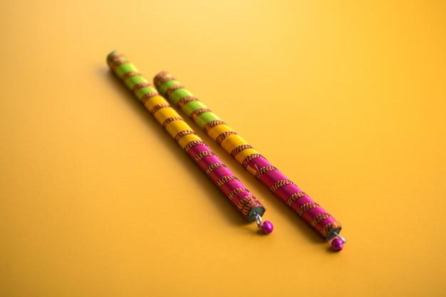 Dandiya klebt auf einem gelben hintergrund. raas garba oder dandiya raas ist der traditionelle volkstanz aus dem indischen bundesstaat gujarat & rajasthan.