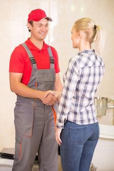 Dank der jungen frau für klempnerarbeit im badezimmer.
