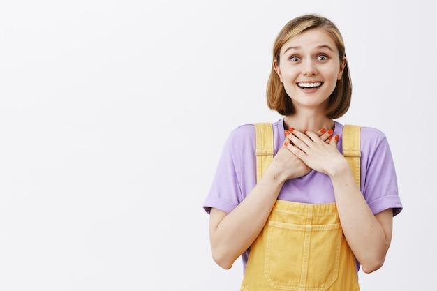 Dankbar glückliche und berührte junge frau, die hände auf herz hält und dankbar lächelt, erhalten chance