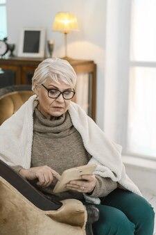 Dankbare alte dame, die ihre tafel benutzt