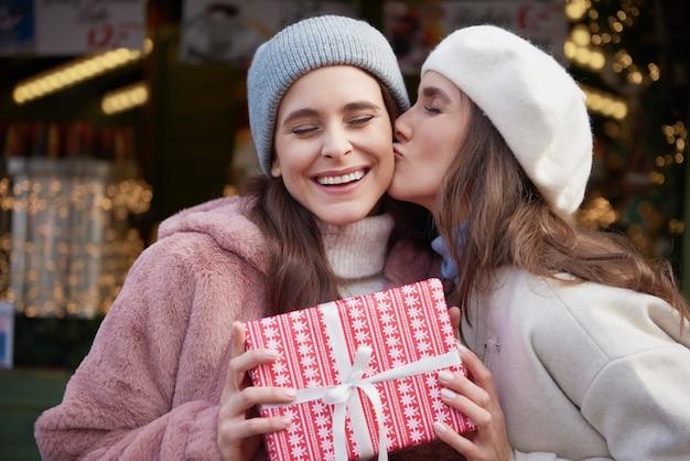 Dankbare frau, die einen kuss auf weihnachtsmarkt gibt
