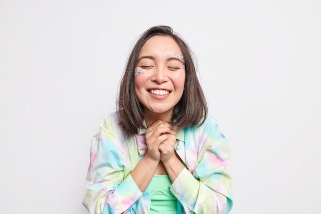 Dankbare positive asiatische frau klammert sich an die hände, hat ein schönheitsgesicht, das mit zähnen lächelt, hält die augen geschlossen, gekleidet in einem lässigen bunten hemd erwartet etwas sehr angenehmes isoliert über weißer wand