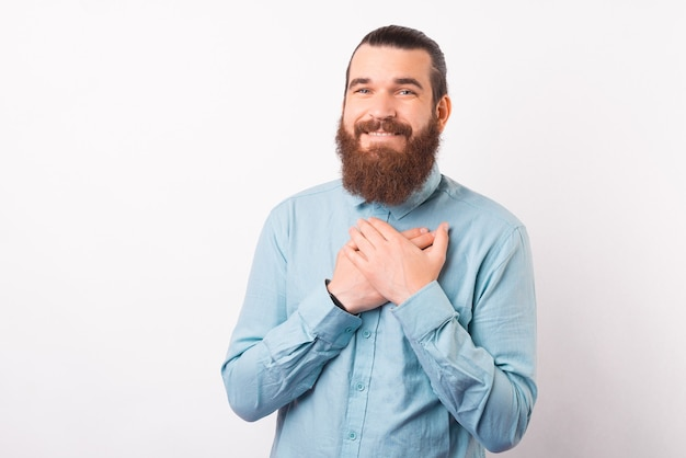 Dankbarer junger bärtiger mann hält die hände an seiner brust.