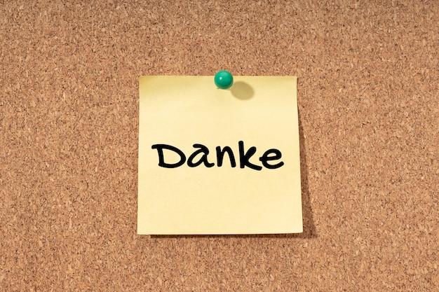 Danke auf deutsch auf gelbem posten auf korckbretthintergrund geschrieben