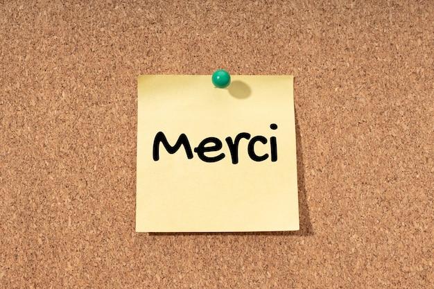 Danke auf französisch auf gelbem posten auf korckbretthintergrund geschrieben