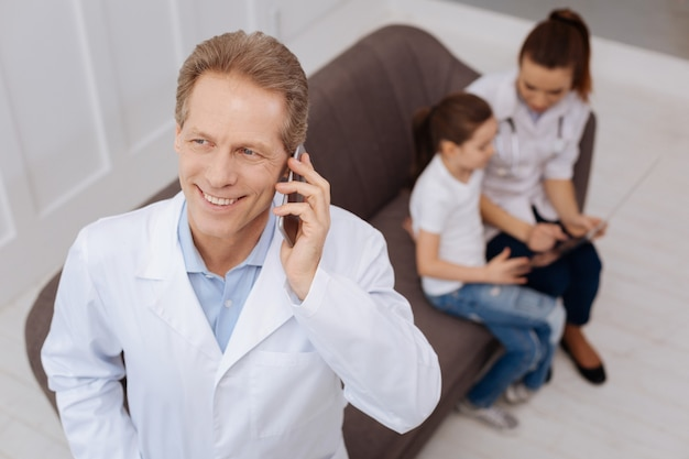 Danke für die hilfe. sehr geehrter, gutaussehender kinderarzt, der mit seinem kollegen telefoniert und um einen gefallen bittet, während eine krankenschwester ihrem kleinen patienten etwas erklärt