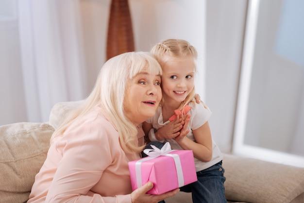 Danke für ein geschenk. erfreute nette alte frau, die lächelt und eine geschenkbox hält, während sie ihre enkelin umarmt
