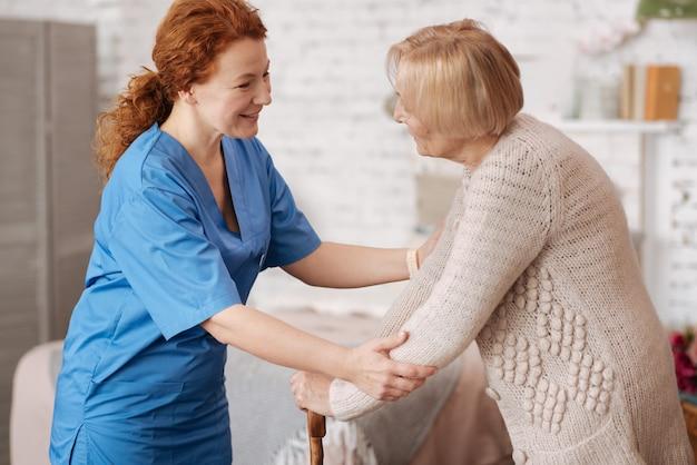 Danke fürs kommen. charmante aktive ältere dame, die eine medizinische mitarbeiterin begrüßt, die sie jede woche besucht und sich um ihre gesundheit kümmert