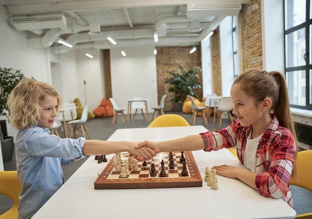 Danke kaukasischer junge und mädchen, die sich anschauen und sich die hände schütteln, nachdem sie schach gespielt haben