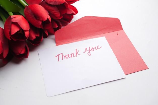 Danke nachrichtenumschlag und rote tulpenblume auf weißem hintergrund