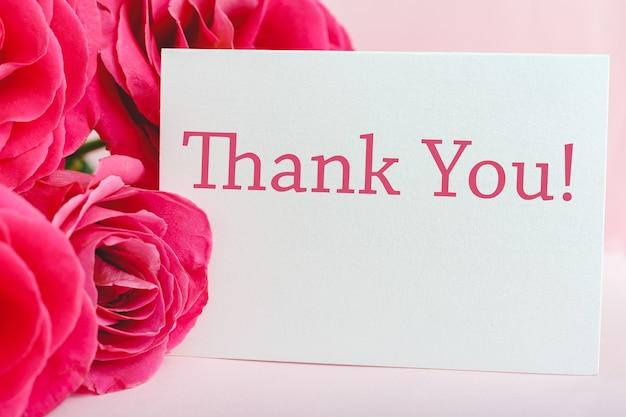 Dankeschön-karte im schönen blumenstrauß aus rosa rosen auf rosa hintergrund. weiße leere karte mit platz für text, rahmenmodell für einladung. frühlingsfeste blumen
